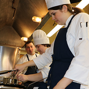 Three students in a kitchen performing various cooking techniques