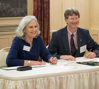 Presidents from Drew University and Sussex sign an agreement at the table