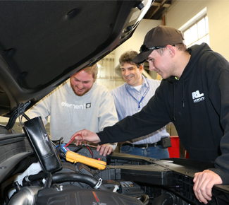 Two automotive students lean over a car with their instructor.