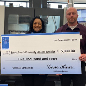 2 people, woman and man, hold a large over sized check in the amount of $5000.