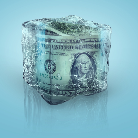Blue background with a roll of money frozen in an ice block.