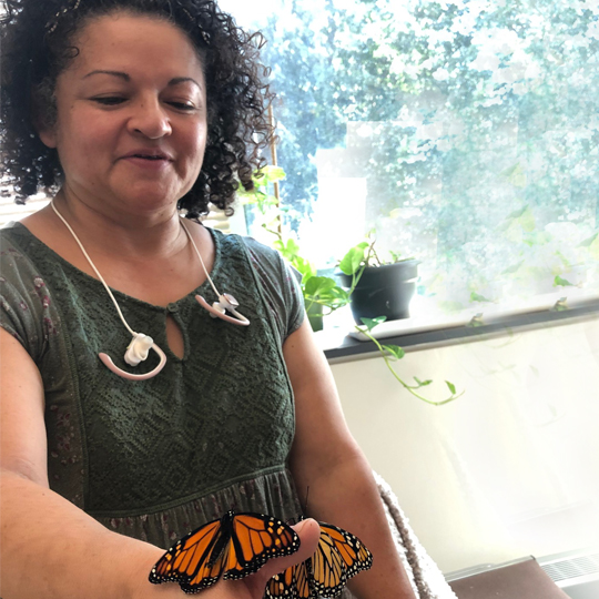 An older student stands with 2 butterflies on her hand.