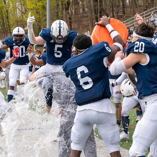 Football players dump a buck of water of the coach after their victory